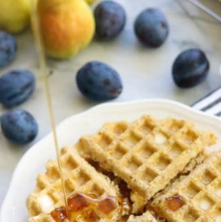 overhead shot of vegan waffles quartered on white plate with maple syrup being drizzled over