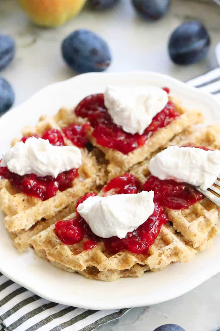 overhead view of vegan waffles quartered on a white plate and topped with plum jam and vegan whipped cream