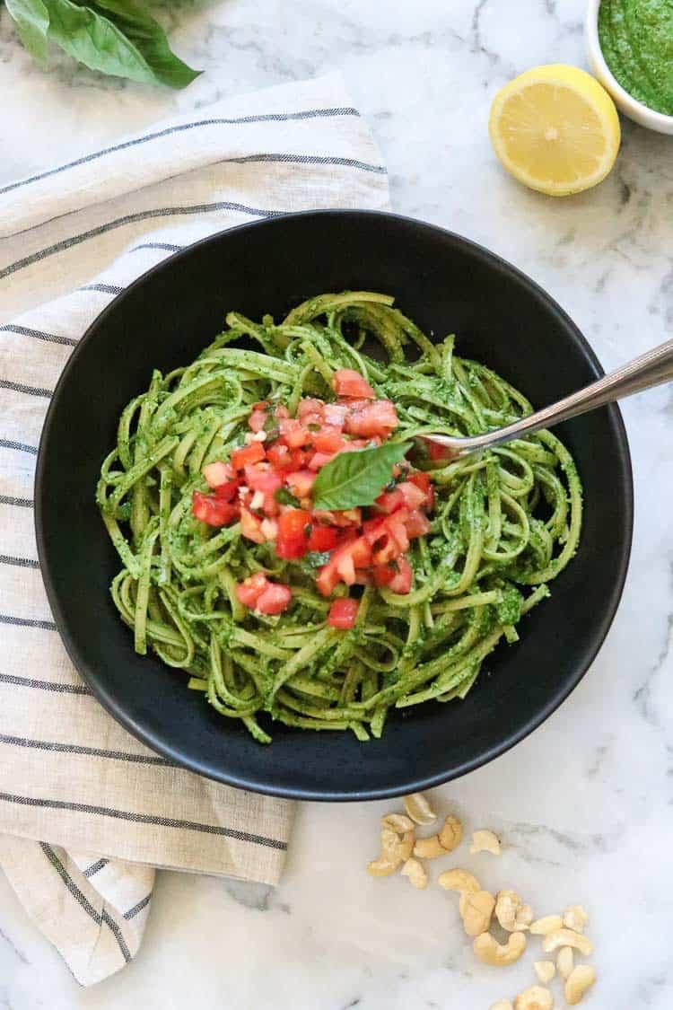 overhead shot of vegan pesto on pasta with tomato bruschetta in the center