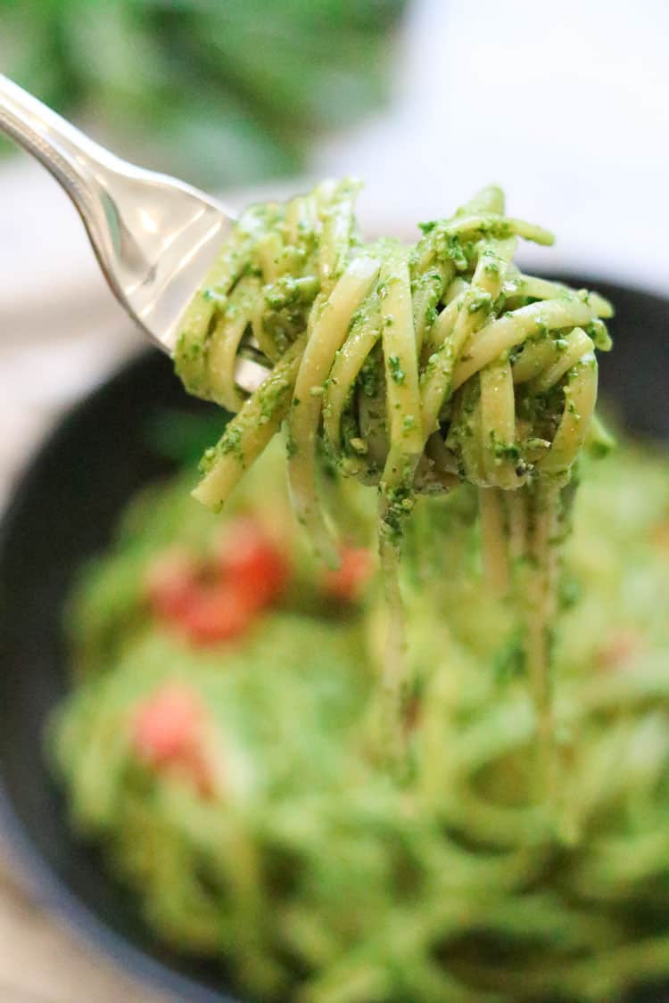 side closeup view of vegan pesto pasta wound on a fork