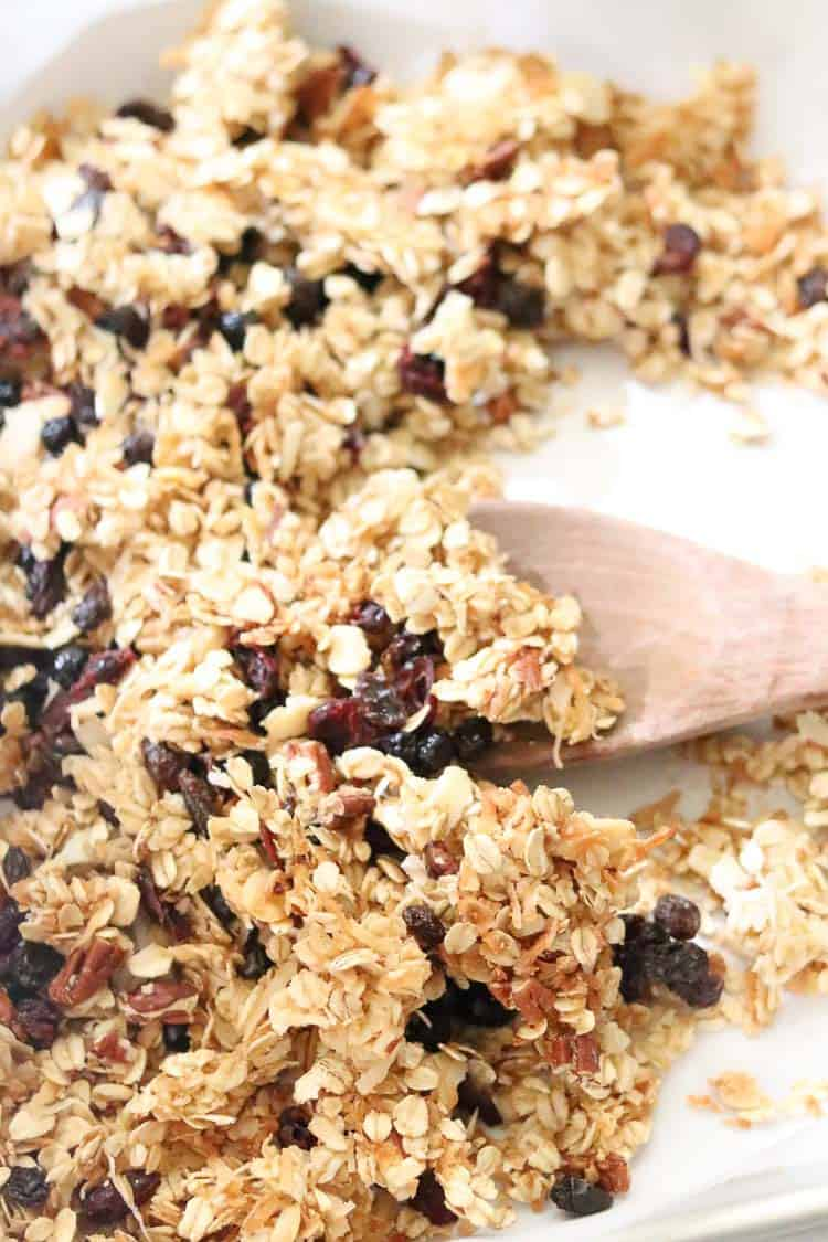 side closeup shot of vegan granola on a tray with wooden spoon