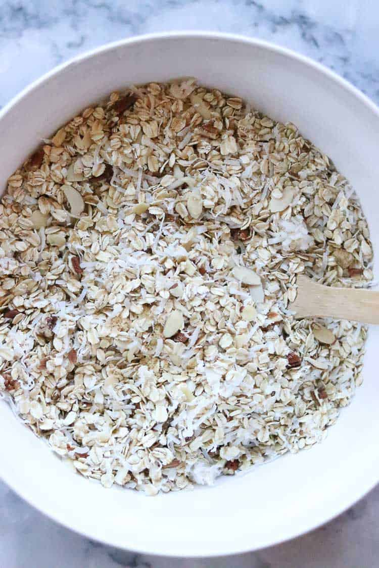 overhead shot of oats, nuts and coconut being mixed for vegan granola