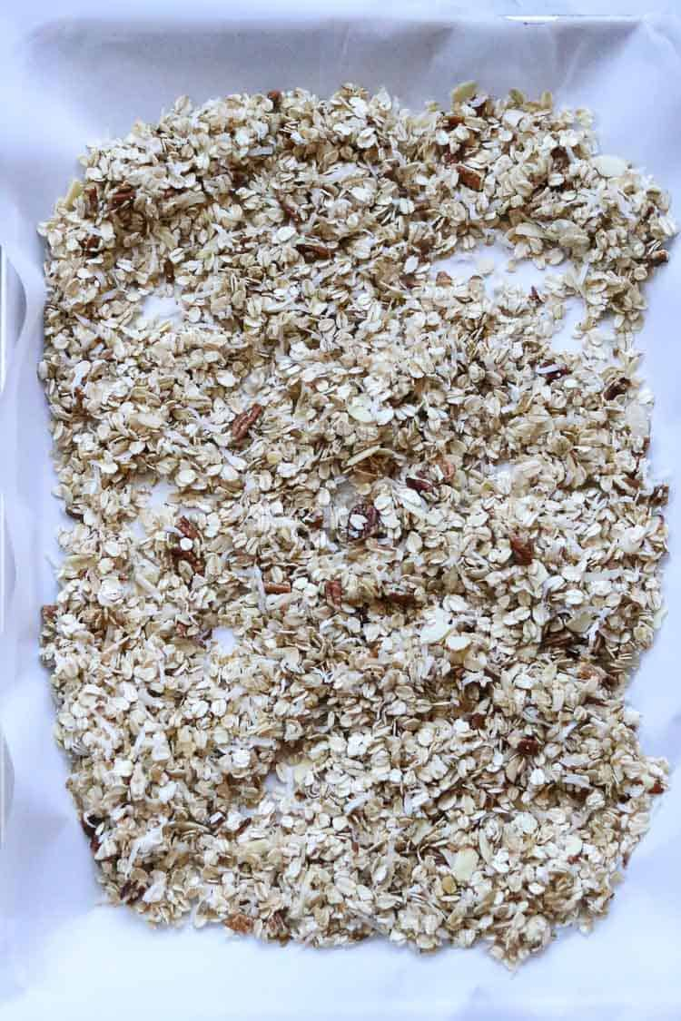 overhead shot of vegan granola on a parchment paper lined baking tray