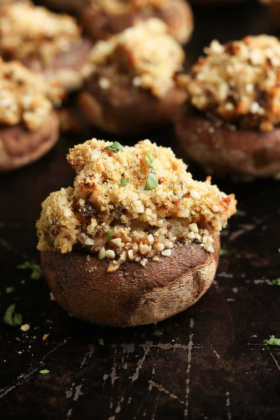 side overhead photo of single stuffed mushroom with fresh chopped herbs sprinkled over