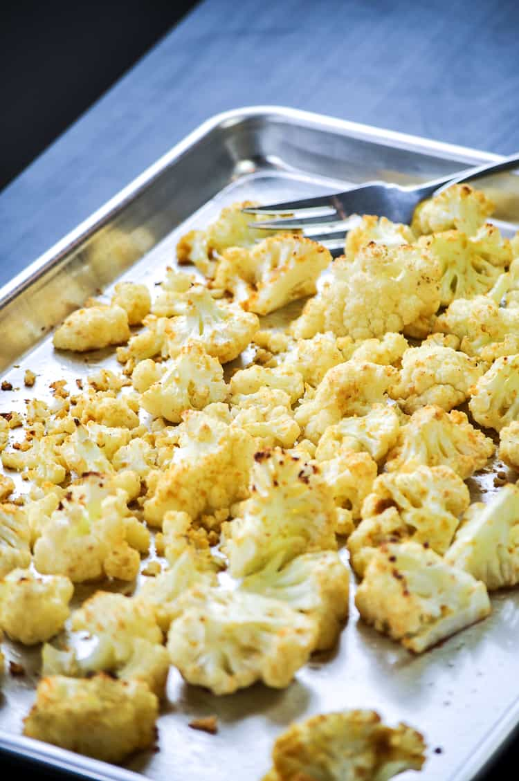 side overhead shot of crispy baked cauliflower on a silver baking tray