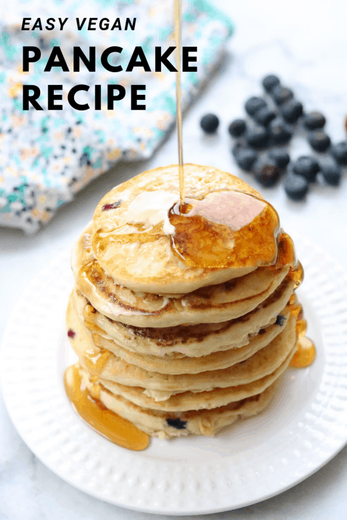 side overhead shot of stack of vegan pancakes on a white plate with maple syrup being poured over with text overlay