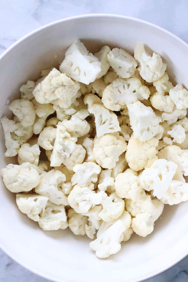 overhead shot of cauliflower florets in a white mixing bowl