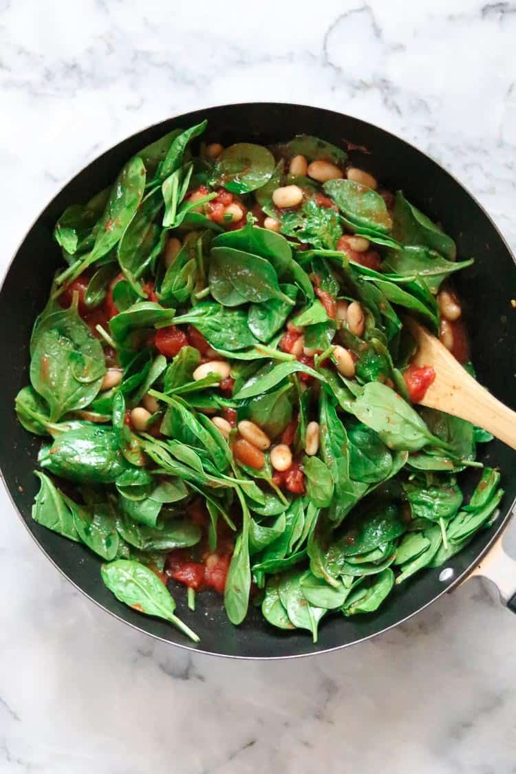 overhead shot of baby spinach being folded into pasta sauce with Cannellini beans in skillet