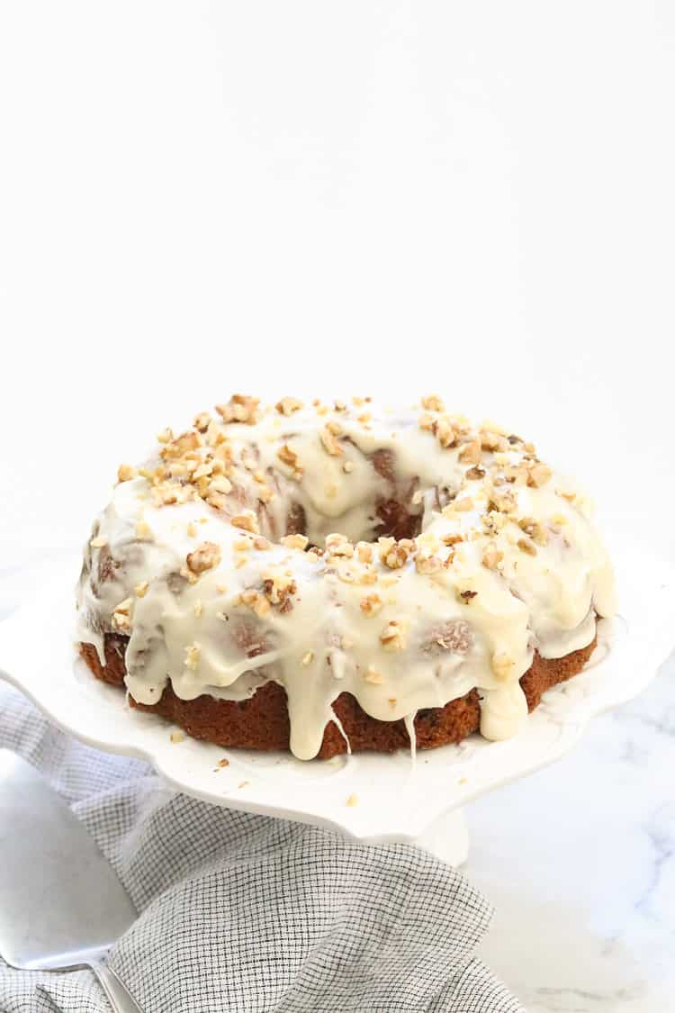 side overhead shot of frosted vegan carrot cake on a white cake plate