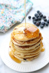 side overhead shot of maple syrup being poured over a stack of pancakes on a white plate