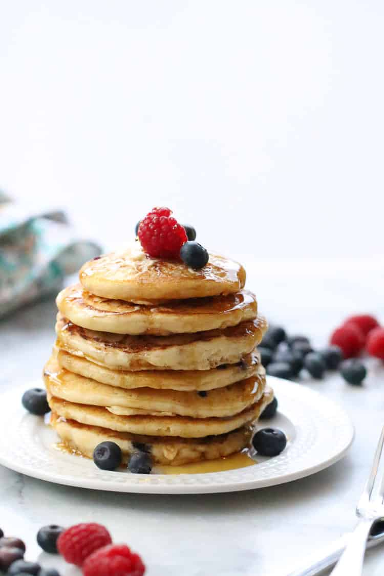 side shot of vegan buttermilk pancakes stacked tall on a white plate with utensils nearby and garnished with fresh blueberries and raspberries