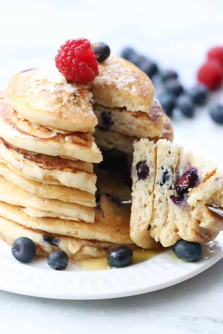 Side shot of sliced stack of vegan pancakes with several large pieces on a fork with maple syrup and fresh berries as a garnish