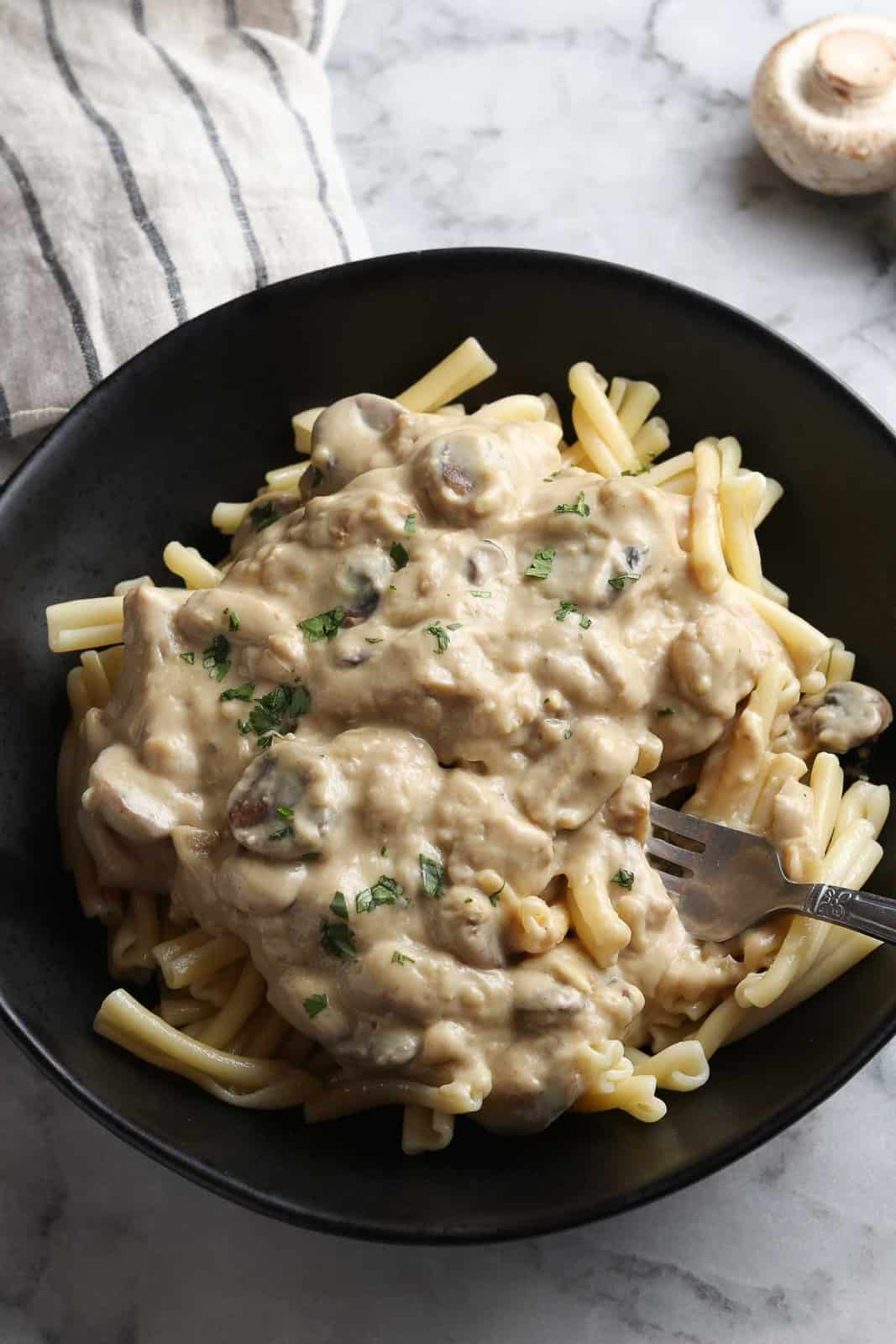 side overhead closeup of vegan stroganoff with a fork digging into the bowl of pasta and sauce