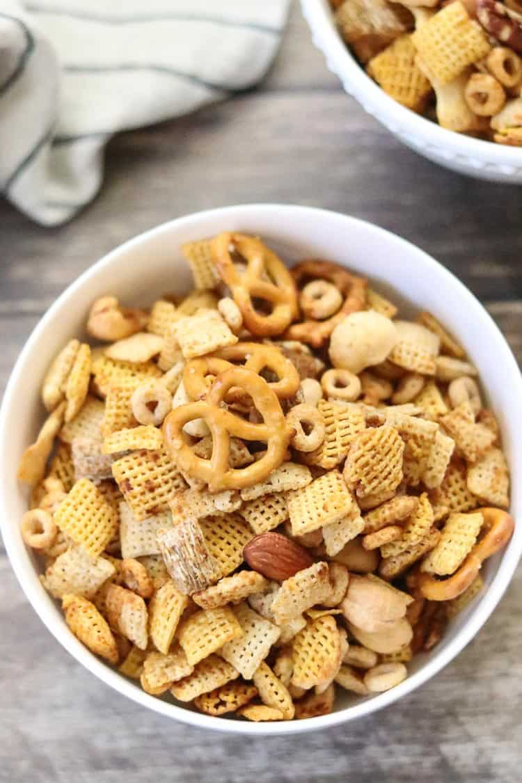 overhead shot of chex mix in white bowl on brown wooden background with napkin beside