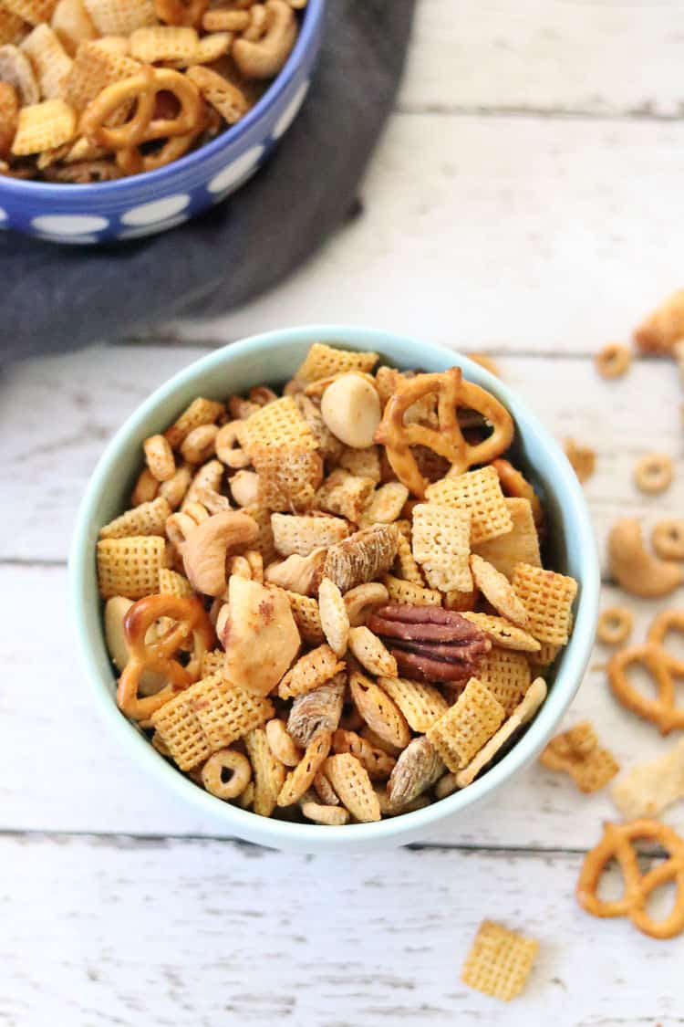overhead shot of vegan Chex mix in turquoise bowl with another bowl and napkin beside