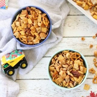 Overhead shot of vegan chex mix in blue bowls with napkin beside