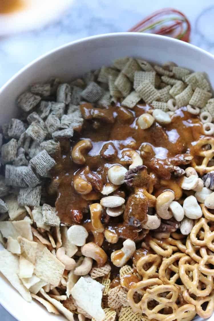 overhead shot of sauce for vegan Chex mix poured over ingredients in white bowl