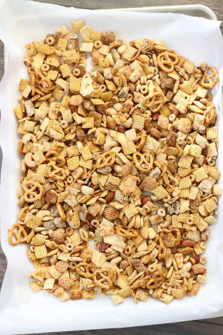 overhead shot of vegan Chex mix on white parchment paper on baking tray