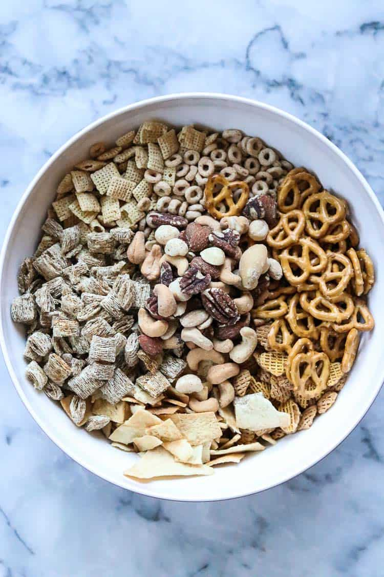 overhead shot of dry ingredients for vegan chex mix in white bowl