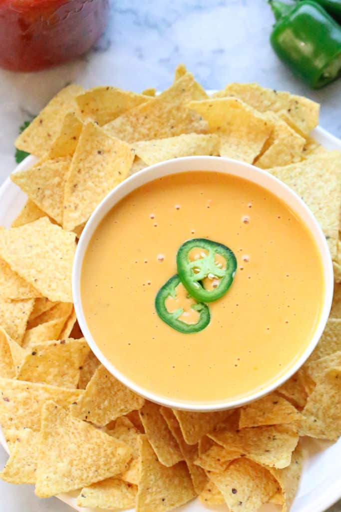 Overhead Photo of vegan cheese sauce in a white bowl surrounded by nacho chips and decorated with sliced jalapeño