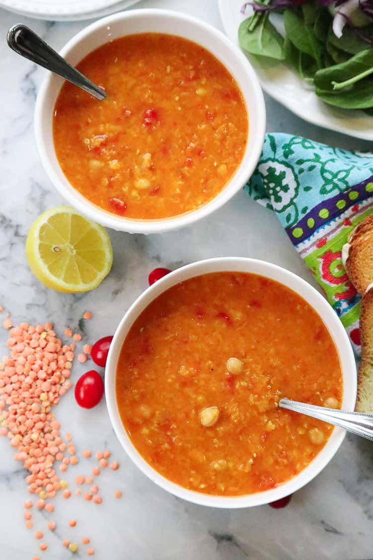 overhead shot of chickpea mediterranean lentil soup in two bowls with slice of lemon beside