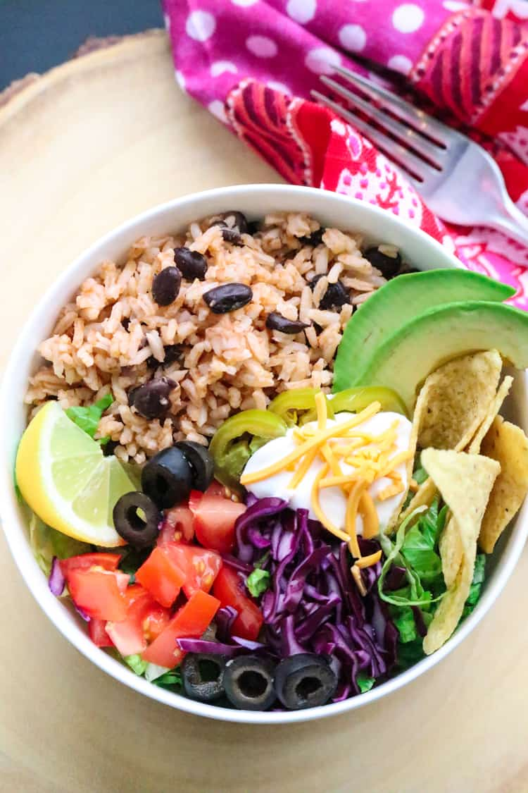 Overhead Shot of Vegan Mexican Rice and Black Beans in a white bowl with bright pink napkin and fork beside.