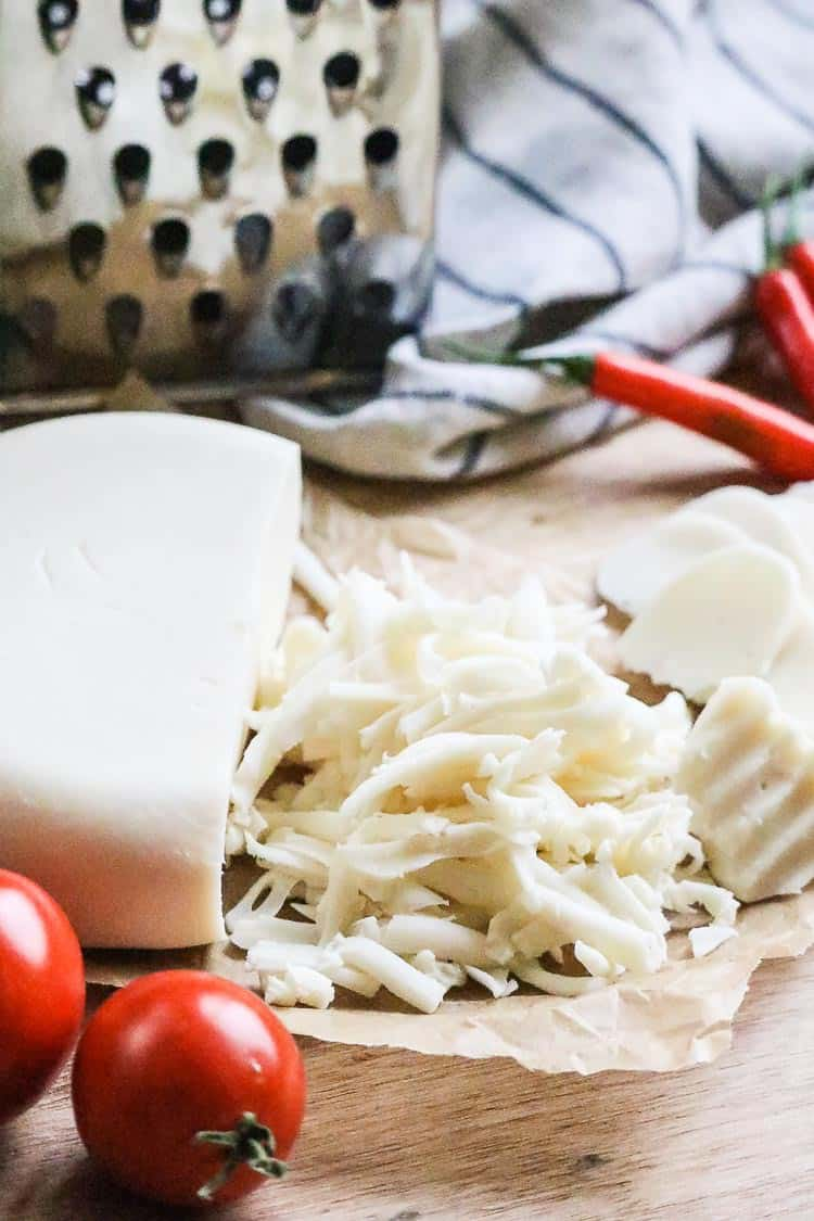 side view of vegan mozzarella cheese sliced and grated with red peppers and tomatoes beside.