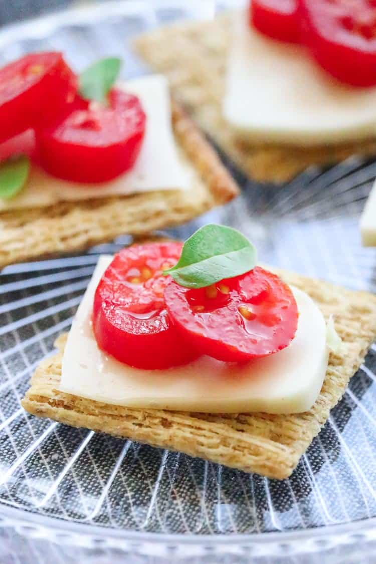 Side view of sliced vegan mozzarella cheese on a cracker with tomato slices and a basil leaf.