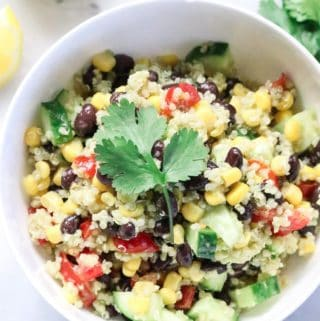 Overhead view of quinoa salad in white bowl with sprig of cilantro.