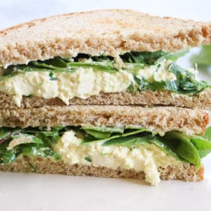 Side View of cut and stacked vegan egg salad sandwiches on a plate