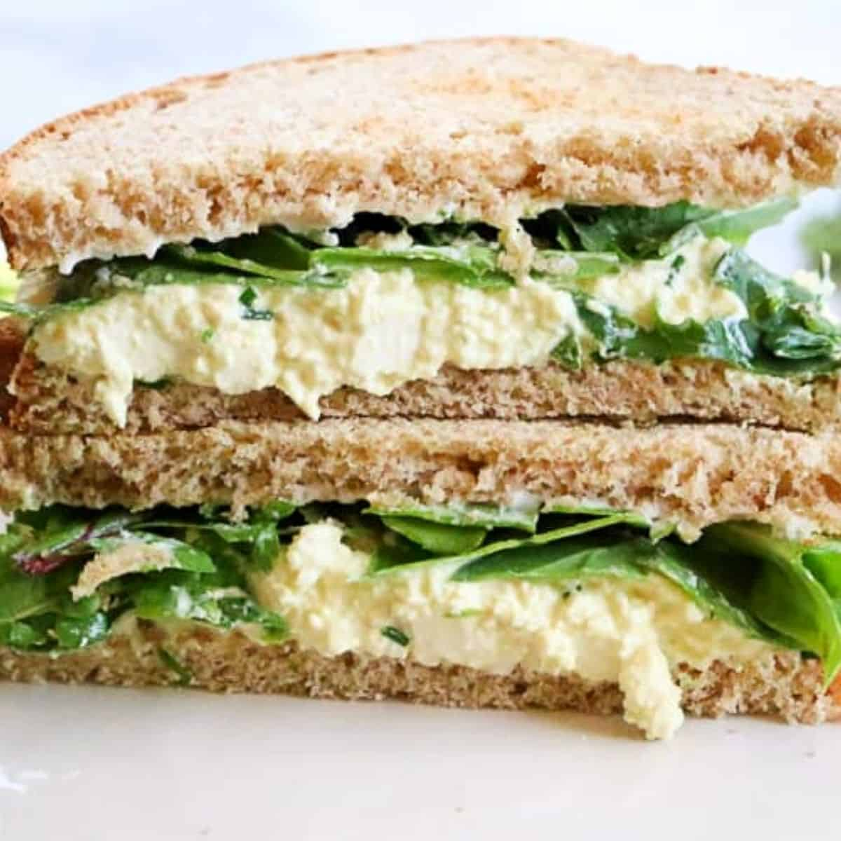 close up image of a vegan egg salad sandwich made with mashed tofu, cut in triangles and stacked on top of each other