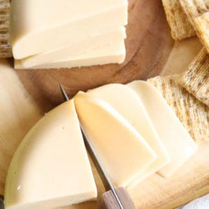 overhead shot of vegan good cheese being sliced with crackers beside