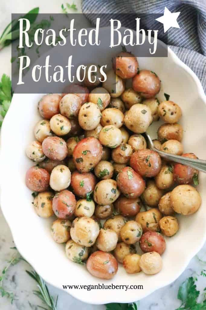 White bowl filled with roasted baby potatoes surrounded by fresh herbs.
