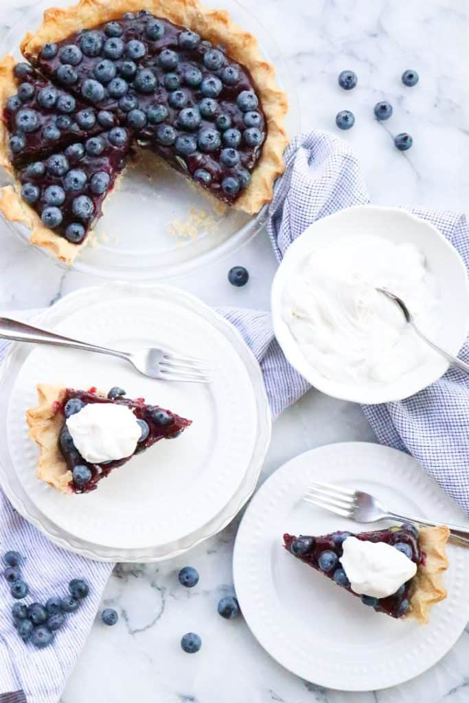 Overhead shot of sliced blueberry pie on white plates with napkins and blueberries surrounding