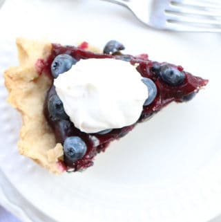 Overhead shot of Easy Blueberry pie on a plate with a dollop of whipped coconut cream.