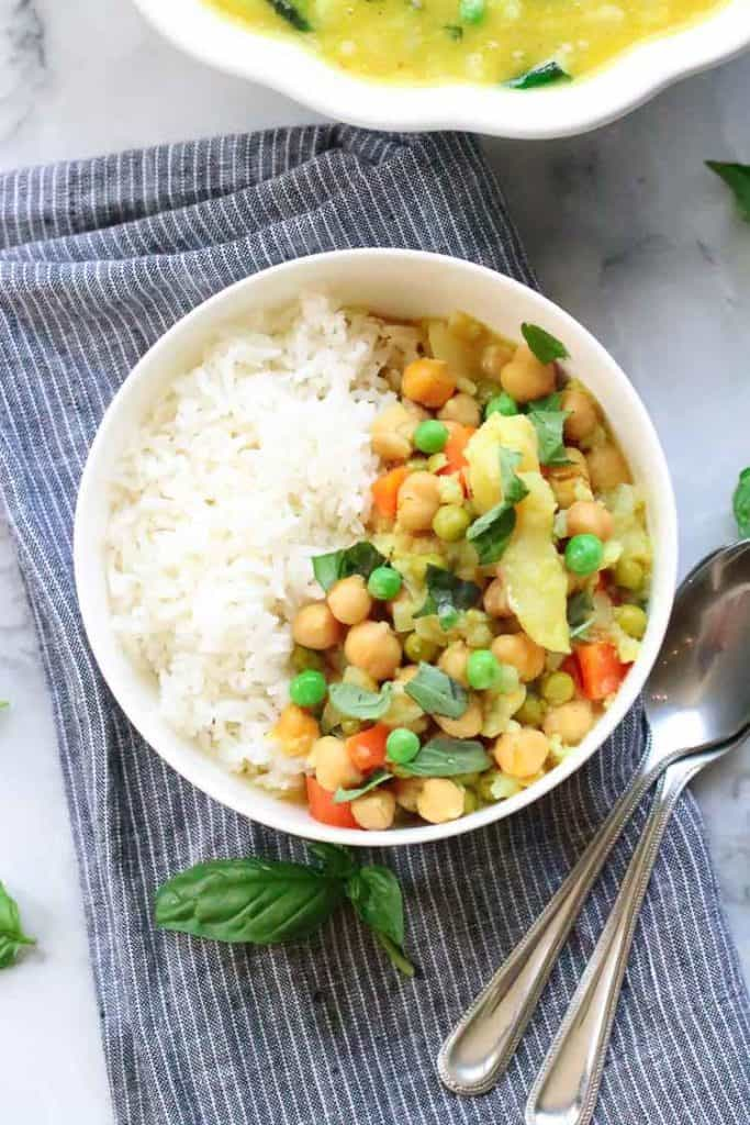 Closeup view of rice and vegan chickpea cauliflower curry in bowl with garnish of basil.