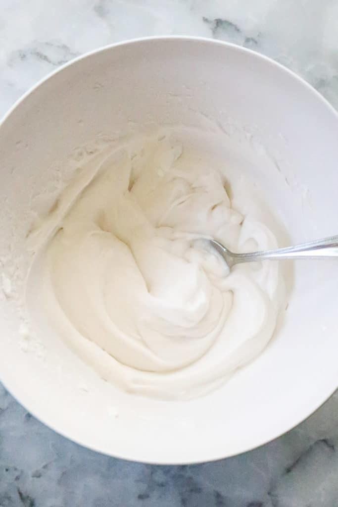 Process shot of Easy Vegan Coconut whip cream all mixed together in a white bowl.