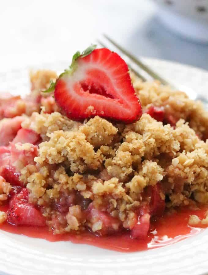 Closeup shot of Strawberry Rhubarb Crisp on a plate with a fork beside and a sliced strawberry on top