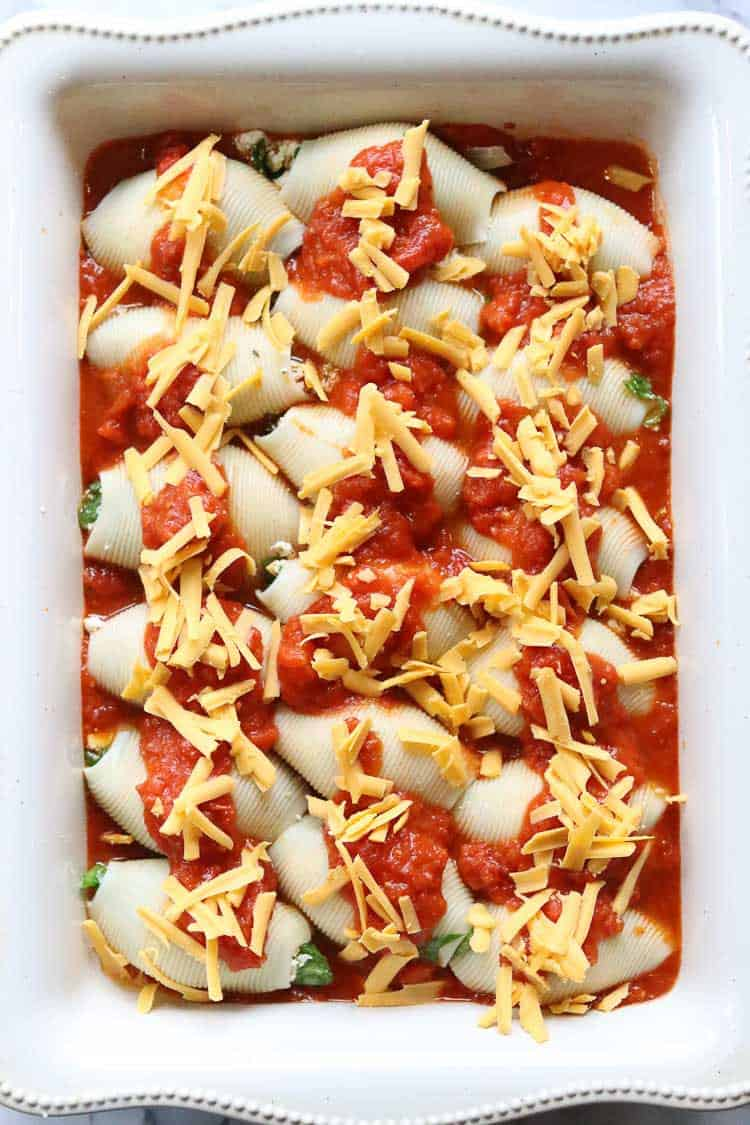 overhead shot of vegan stuffed shells with a drizzle of red sauce and a garnish of vegan cheese