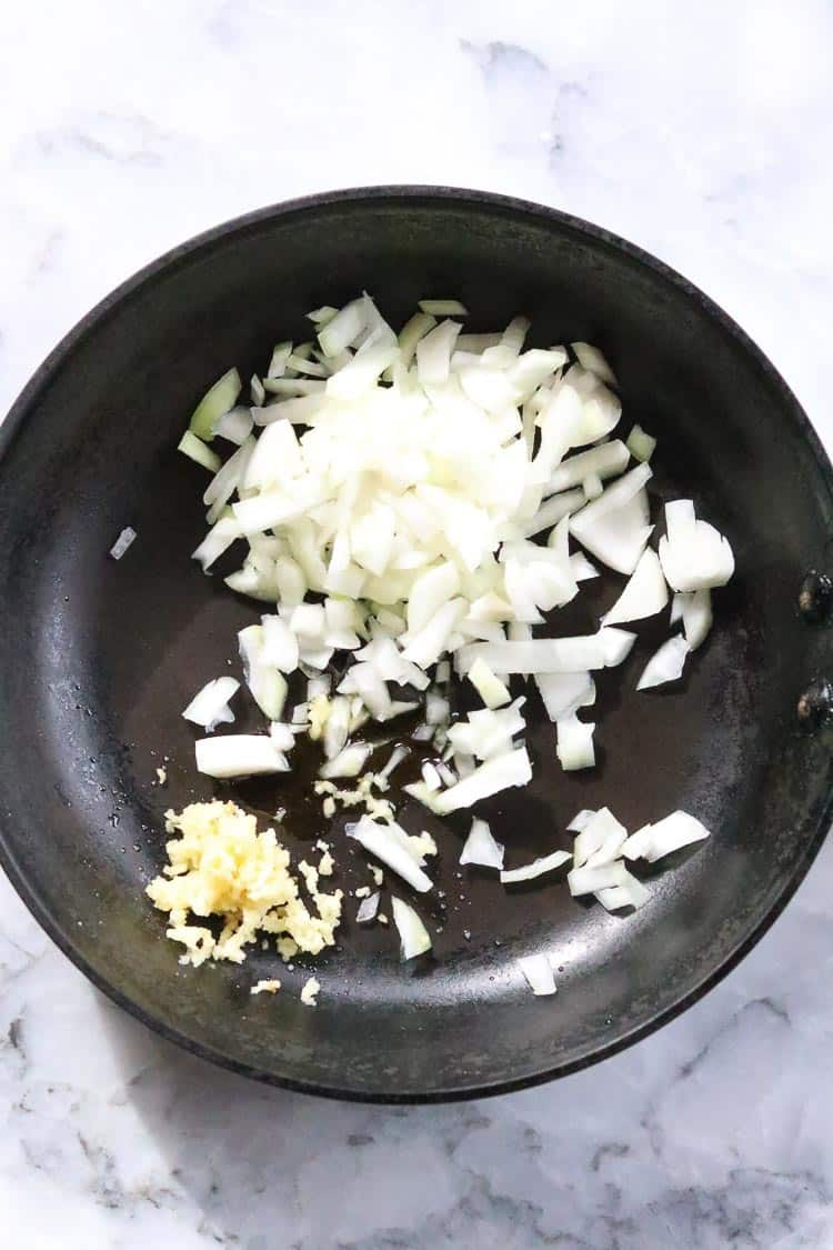 Overhead shot of chopped onion and garlic in a frying pan