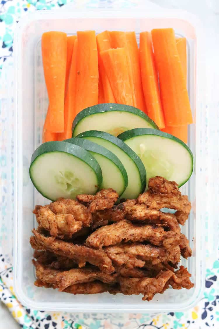 Overhead shot of vegan jerky in a lunch container with sliced cucumbers and carrots