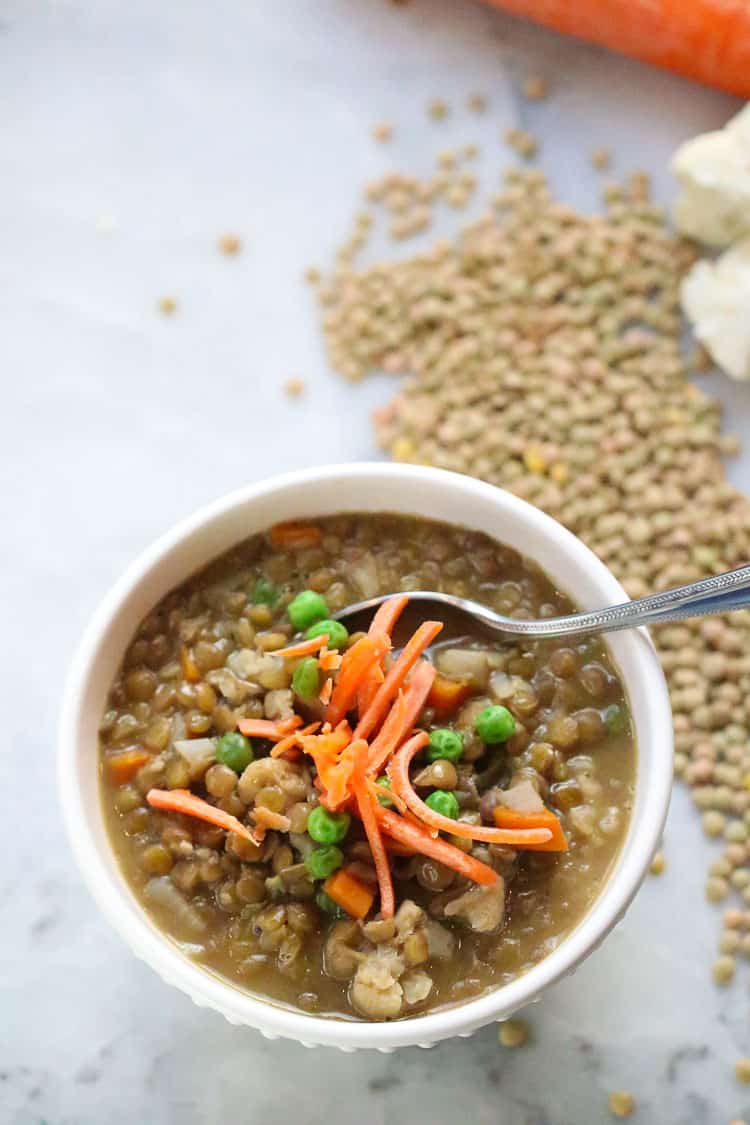 overhead shot of one white bowl filled with vegan lentil soup and garnished with shredded carrots and peas