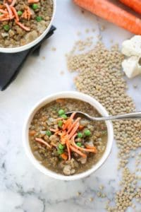 overhead shot of vegan lentil soup in two white bowls with dried brown lentils beside on marble background