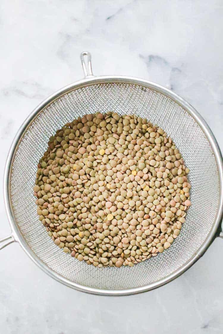 overhead shot of dried brown lentils in a colander