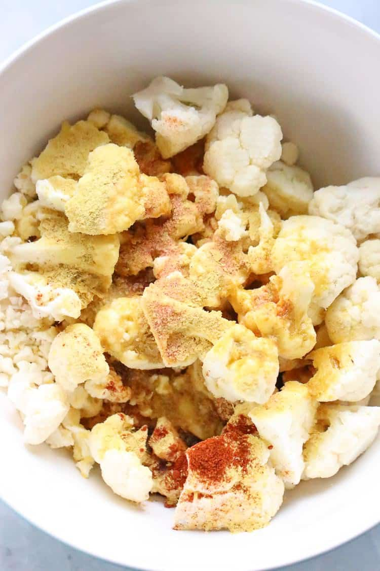 seasonings and olive oil sprinkled on cauliflower florets in a white bowl