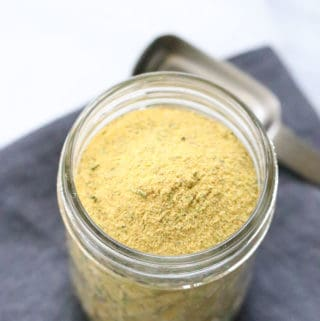 overhead shot of vegan chicken seasoning in a small clear jar with teaspoon beside