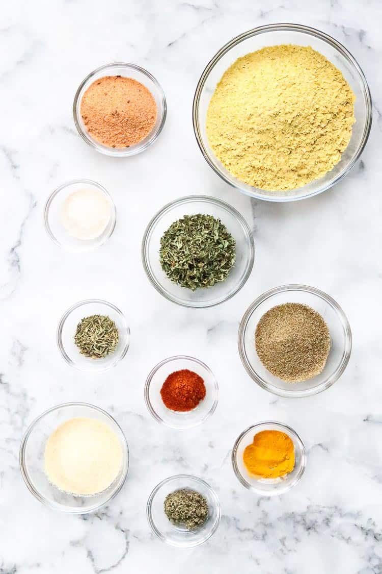 overhead photo of seasonings in small clear bowls for vegan chicken-style broth