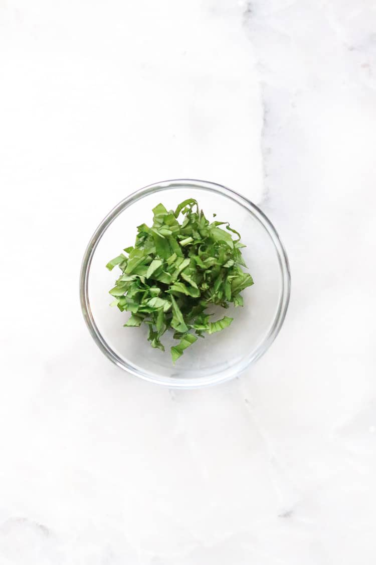 small clear bowl of chopped basil