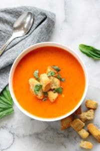 overhead shot of vegan tomato soup in a white bowl with garnish of croutons and chopped spinach