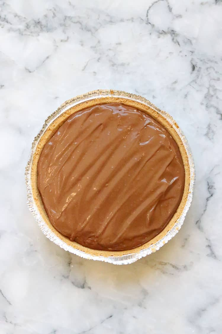overhead shot of graham cracker crust filled with peanut butter pie filling
